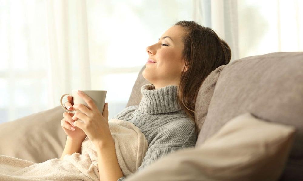 Un femme qui relaxe à l'intérieur au chaud en hiver