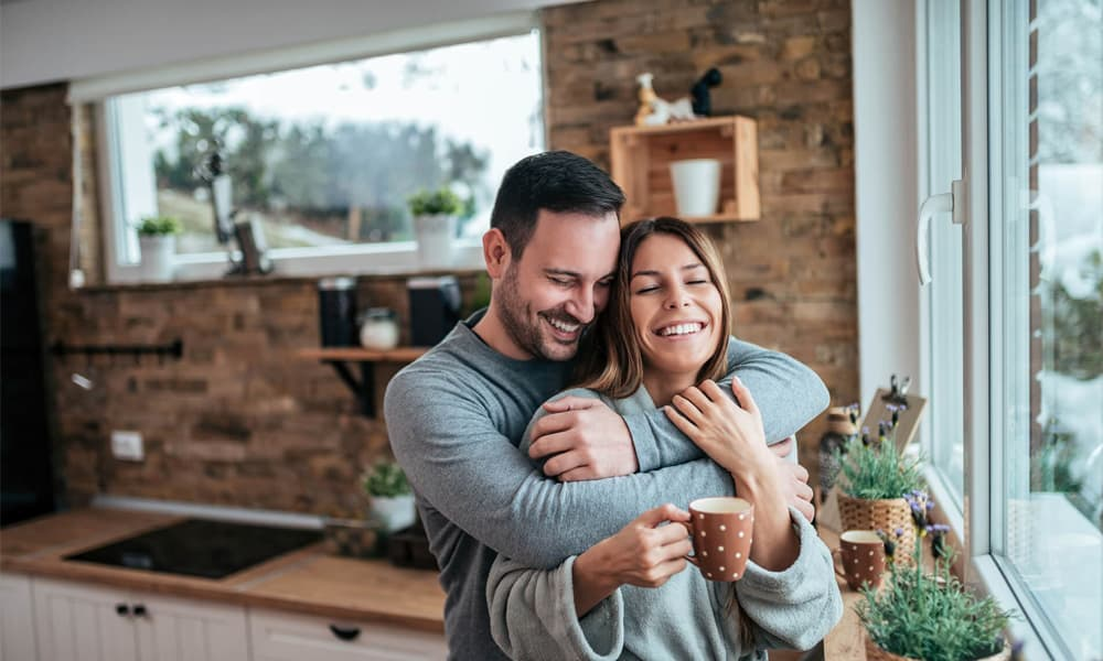 Man hugging a woman holding a cup of coffee in home with air conditioning in Montreal