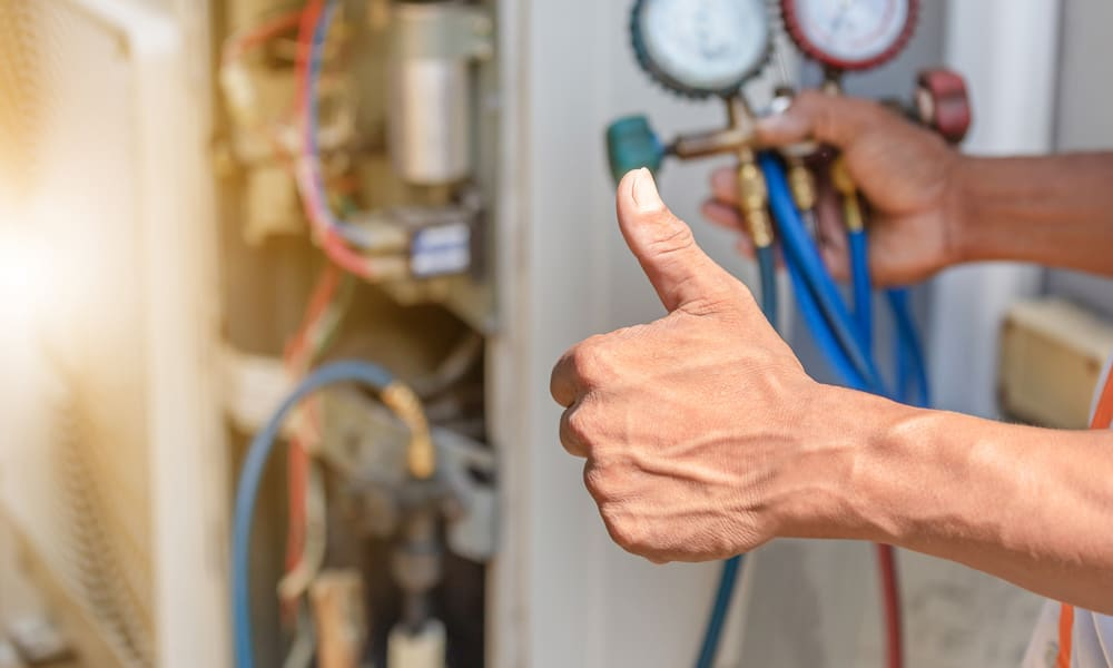 An HVAC technician showing the thumbs up after installing a central air conditioner