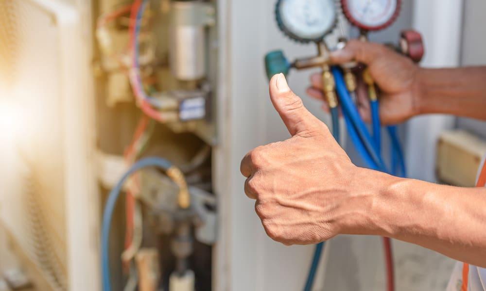 Un technicien en chauffage qui répare une thermopompe