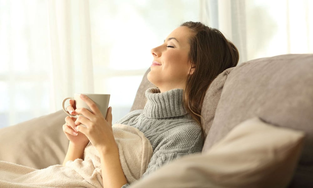 Woman relaxing on a couch with a cup of coffee inside a warm and cozy home during winter
